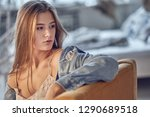 sad woman sitting on a sofa in... | Shutterstock . vector #1290689518