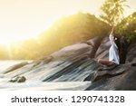 woman yoga meditates on a rock... | Shutterstock . vector #1290741328