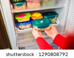 Woman Placing Container With...