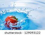 Strawberry falls deeply under water with a splash - stock photo