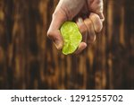 Hand squeeze lime with lime drop on wooden background