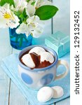 Cup of hot chocolate drink with marshmallow on a blue background. - stock photo