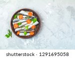 Stock photo sardines or baltic herring with rosemary parsley tomatoes slices and spaces on ceramic plate on 1291695058