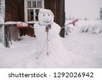 Smiling handmade snowman near the wooden house in snowy winter weather, no people around