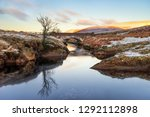 Small photo of Pont Ar Elan, Elan Valey, wales snowy scene of Afon Elan flowing through a bridge in winter with lone tree reflected in water and early morning sun lighting the top of distant mountains