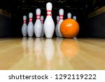 orange bowling ball and white skittles stand on a wooden bowling alley. copy space - stock photo