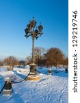 Antique frosty lamppost and beautiful snow covered branches against the azure sky - stock photo