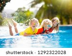 kids play in swimming pool.... | Shutterstock . vector #1292322028