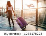 Young Woman Pulling Suitcase In ...