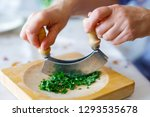 a woman shreds parsley on a...   Shutterstock . vector #1293535678