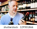 Man in a comparing two wines bottles - stock photo