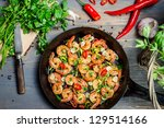 Shrimps fried on pan and fresh herbs - stock photo