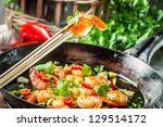 Fried shrimp on chopsticks with herbs - stock photo