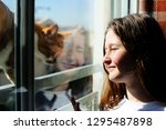 teenage girl looking out of the ... | Shutterstock . vector #1295487898