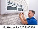 mature male technician fixing... | Shutterstock . vector #1295668318
