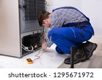side view of a male repairman... | Shutterstock . vector #1295671972