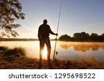 silhouette of angler standing... | Shutterstock . vector #1295698522