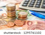 coin piles on euro bills with... | Shutterstock . vector #1295761102