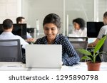 indian worker sitting at desk... | Shutterstock . vector #1295890798