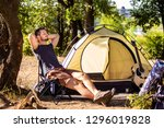 a guy is resting near a tent on ... | Shutterstock . vector #1296019828