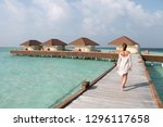 woman in white walking over a... | Shutterstock . vector #1296117658