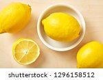 fresh lemon in bowl on wooden... | Shutterstock . vector #1296158512