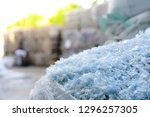 Stock photo close up pet plastic bottle flakes in white big bag with blur plastic bottle bales background 1296257305