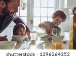 man watching his kid pour milk... | Shutterstock . vector #1296264352