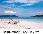 white umbrella stand on beach... | Shutterstock . vector #1296457795