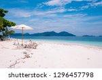 white umbrella stand on beach... | Shutterstock . vector #1296457798