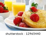 French toast with ripe strawberries, maple syrup and powdered sugar.  A sunny healthy breakfast. - stock photo