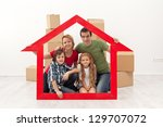 Happy family in their new home - with house shaped frame and cardboard boxes - stock photo