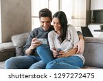 happy young couple sitting on a ... | Shutterstock . vector #1297272475