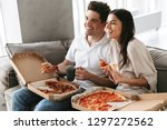 cheerful young couple sitting... | Shutterstock . vector #1297272562