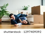 a young couple with cardboard... | Shutterstock . vector #1297409392