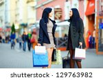 beautiful elegant women walking the crowded city street with shopping bags - stock photo