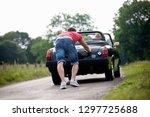 man pushing woman in broken... | Shutterstock . vector #1297725688