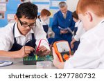 Small photo of High school students using volt meter in electronics class