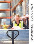 Female warehouse worker with paperwork on pallet smiling at camera