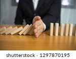businessman hand stops domino... | Shutterstock . vector #1297870195