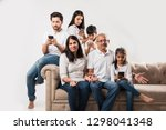 indian family sitting on couch... | Shutterstock . vector #1298041348