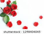 Stock photo top view of three red roses around by rose leaves and rose petals isolated on white background 1298404045