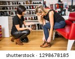 a seller propose to try shoes... | Shutterstock . vector #1298678185