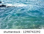 waves splashing against the... | Shutterstock . vector #1298742292