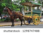 Horse drawn kalesa-calash stopped at Sto.Tomas Street-Plaza de Roma Square at the door of the Cathedral while waiting for passengers visiting the Intramuros-Walled Inner City area. Manila-Philippines.