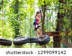 child in forest adventure park. ... | Shutterstock . vector #1299099142