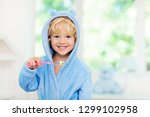 Small photo of Child brushing teeth. Kids tooth brush and paste. Little baby in blue bath robe or towel brushing his teeth in white bathroom with window on sunny morning. Dental hygiene and heath for children.
