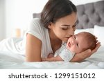 young woman with her newborn... | Shutterstock . vector #1299151012