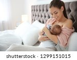 Small photo of Young woman breastfeeding her baby in bedroom