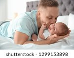 man with his newborn baby on bed | Shutterstock . vector #1299153898